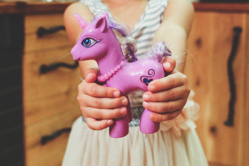 Mädchen hält ein lilafarbenes Einhorn in die Kamera.