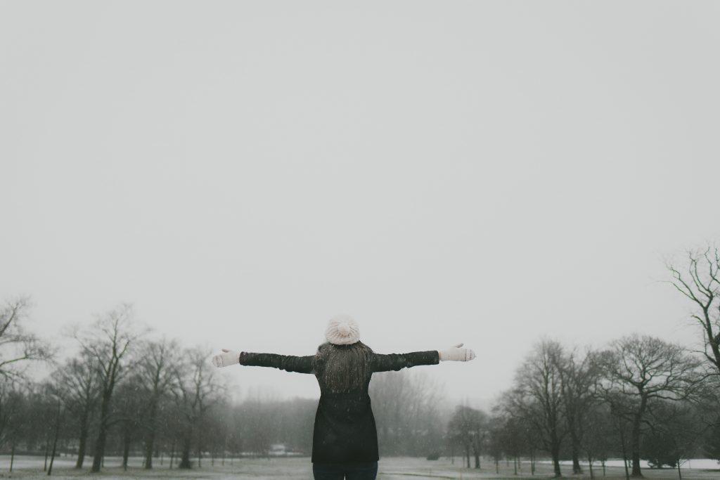 Frau im Winter breitet die Arme aus